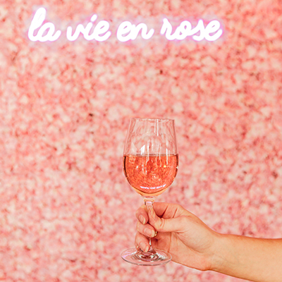 glass of rosé infront of the neon